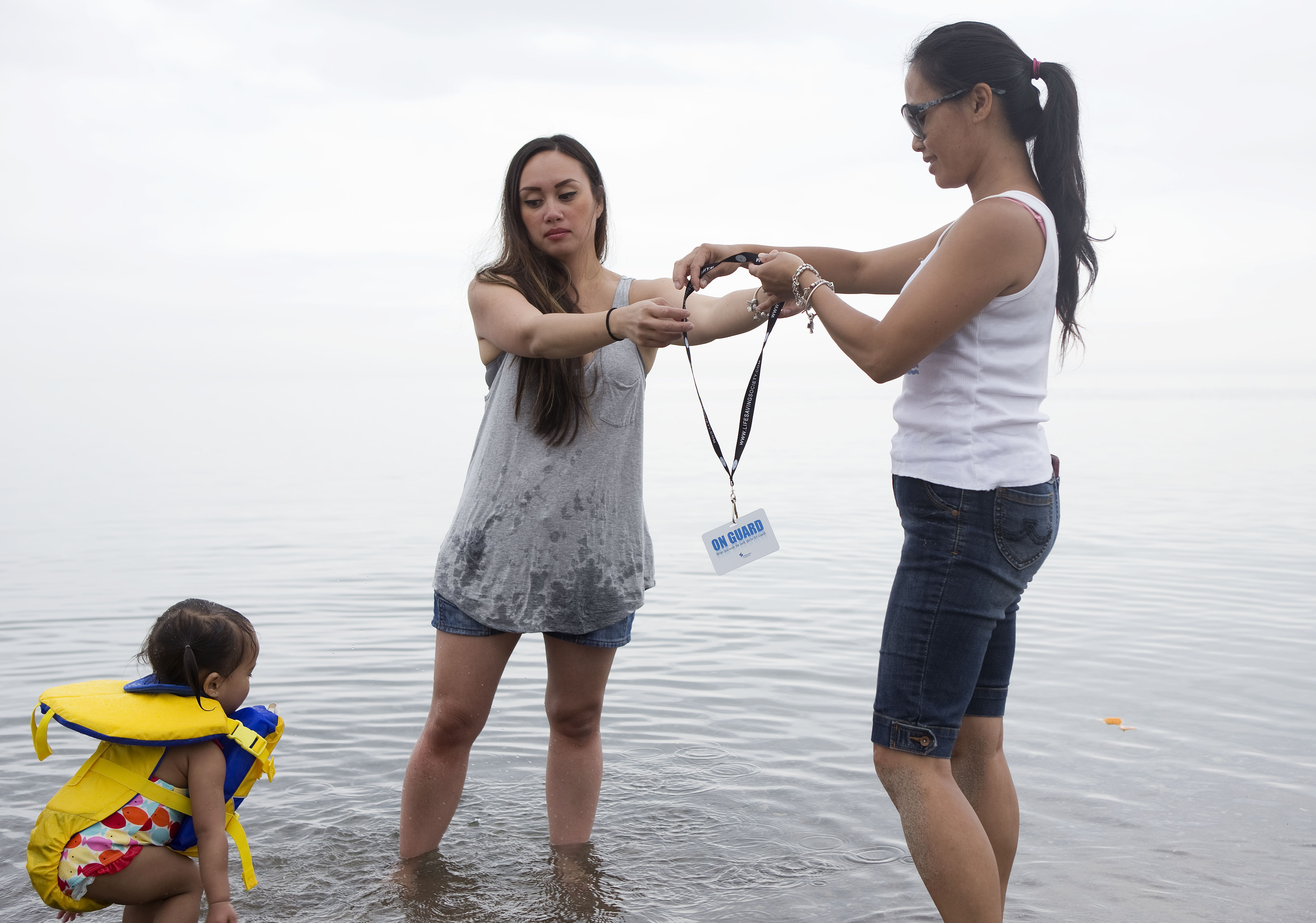 Nadia Luck passes her ON GUARD card to fellow mom Lala de Vera